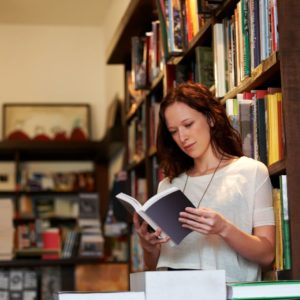 Woman reading a book with shelves of books in background